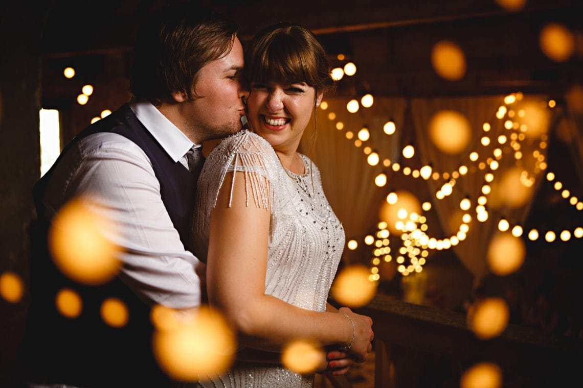The bride and groom having fun in orange lights on their wedding day at Calke abbey in Derbyshire