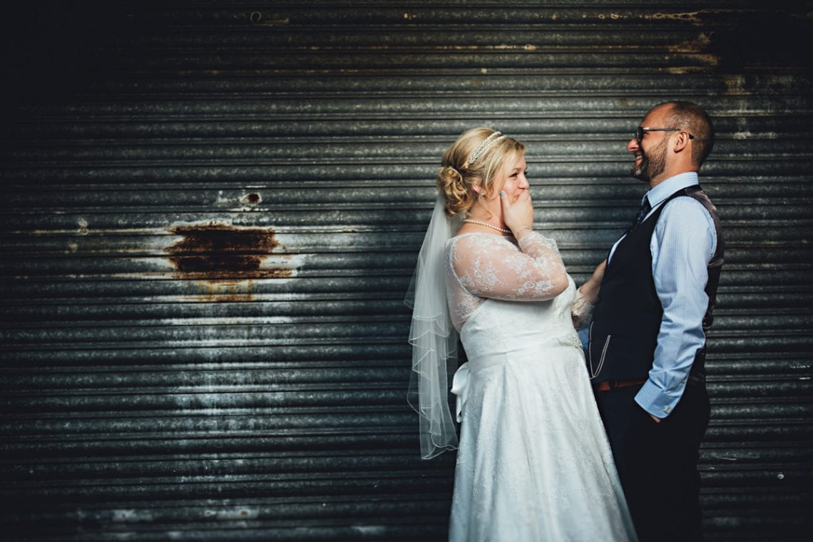 the bride and groom stood by shutter doors having fun on their wedding day in Derbyshire