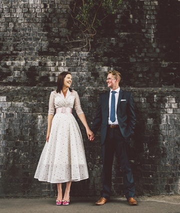 Hannah and Ben, wedding photographers, stood next to each other against a dark brick wall. Ben wearing a blue suit, and Hannah wearing a polkadot dress with pink shoes