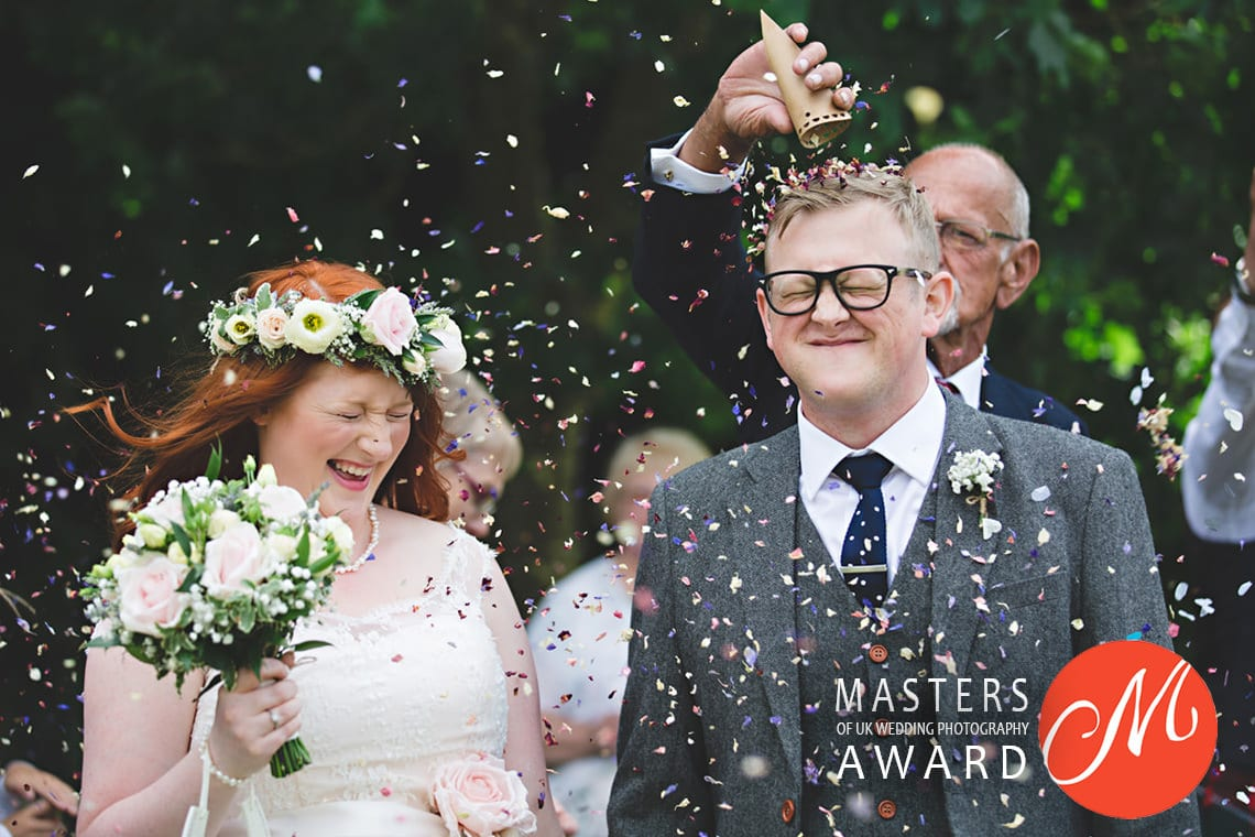 award winning image confetti being thrown over a bride and groom