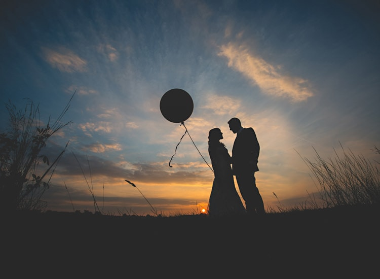 A silhouette of a bride and groom holding a giant balloon in the sunset at Dodford Manor