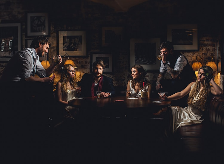 The bridal party, darkly lit in the west mill wedding venue in Derbyshire