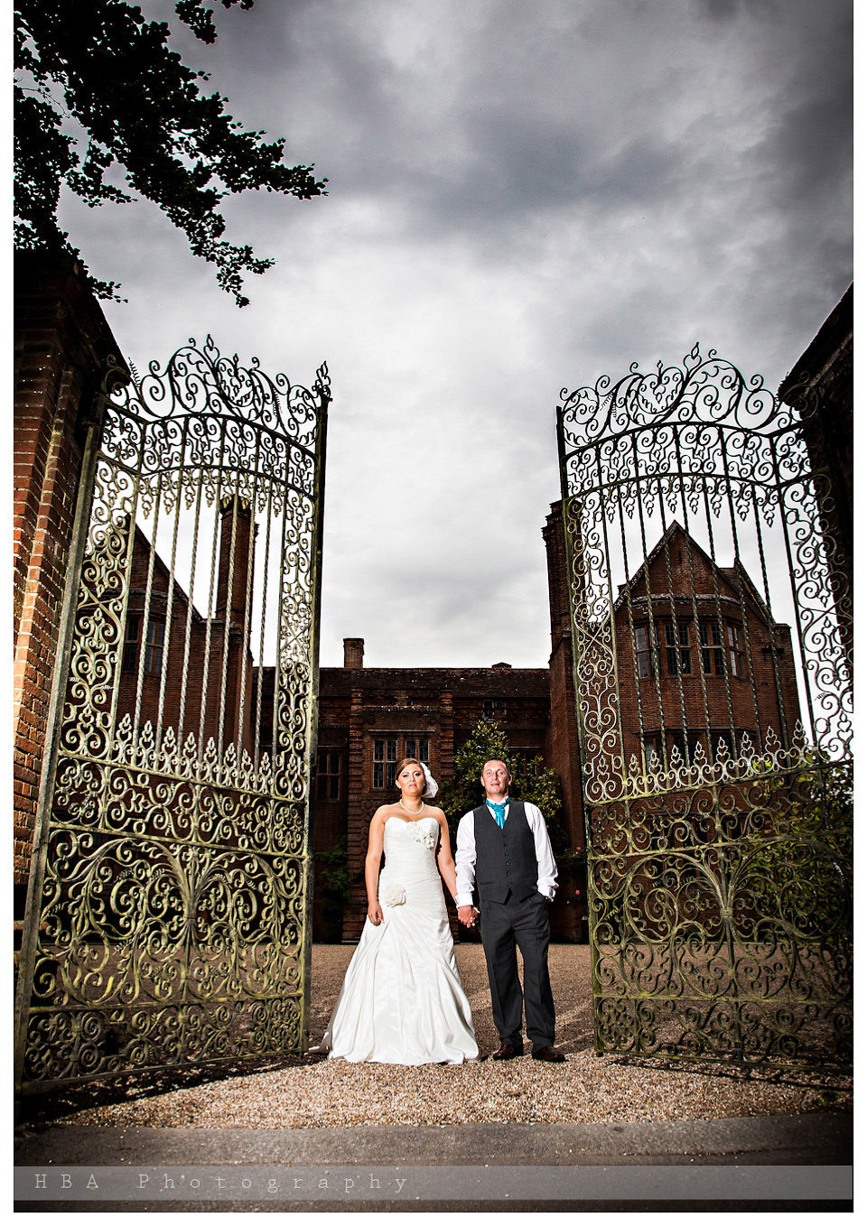 The wedding of Sam & Alan at New Place, Southampton. By contemporary photographers HBA Photography. A bit of drama by the gates of New Place