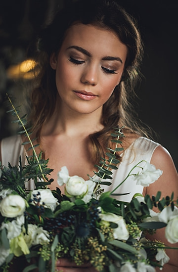A beautiful bride looking down at her flowers at The West Mill wedding venue in Derbyshire