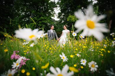 the bride and groom stood in a green field surrounded by wild flowers on their wedding day