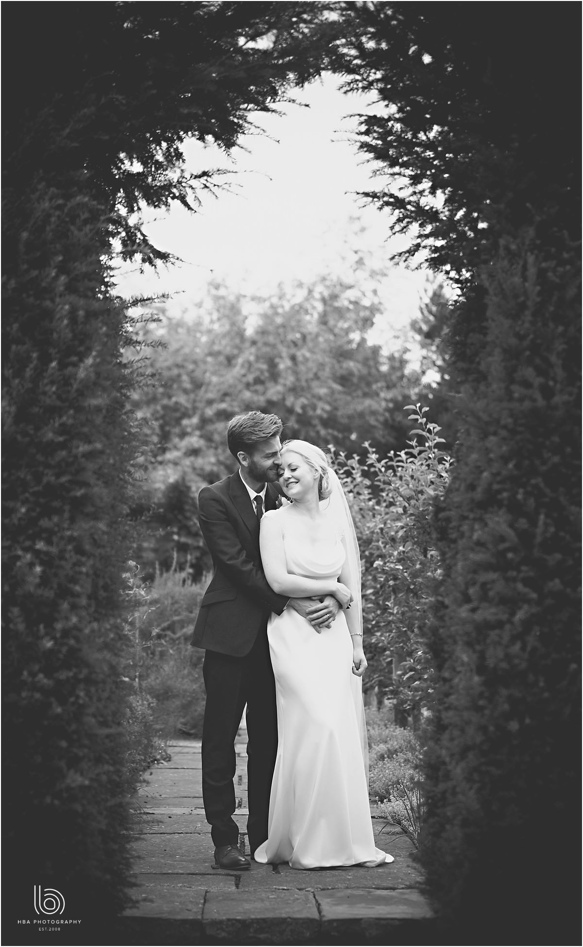 a black and white photo of the bride and groom having a cuddle