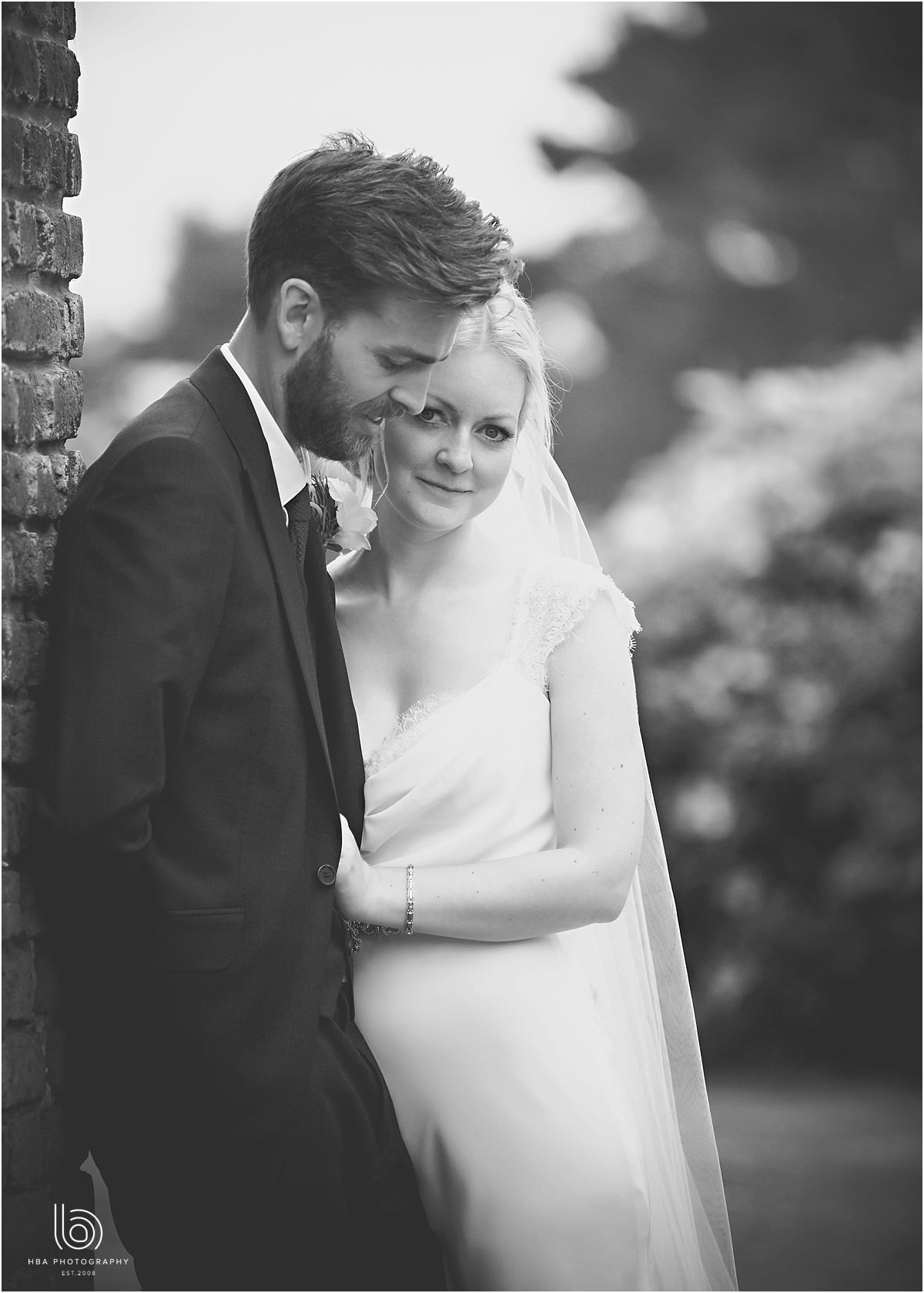 a black and white photo of the bride hugging her husband whilst looking at the camera