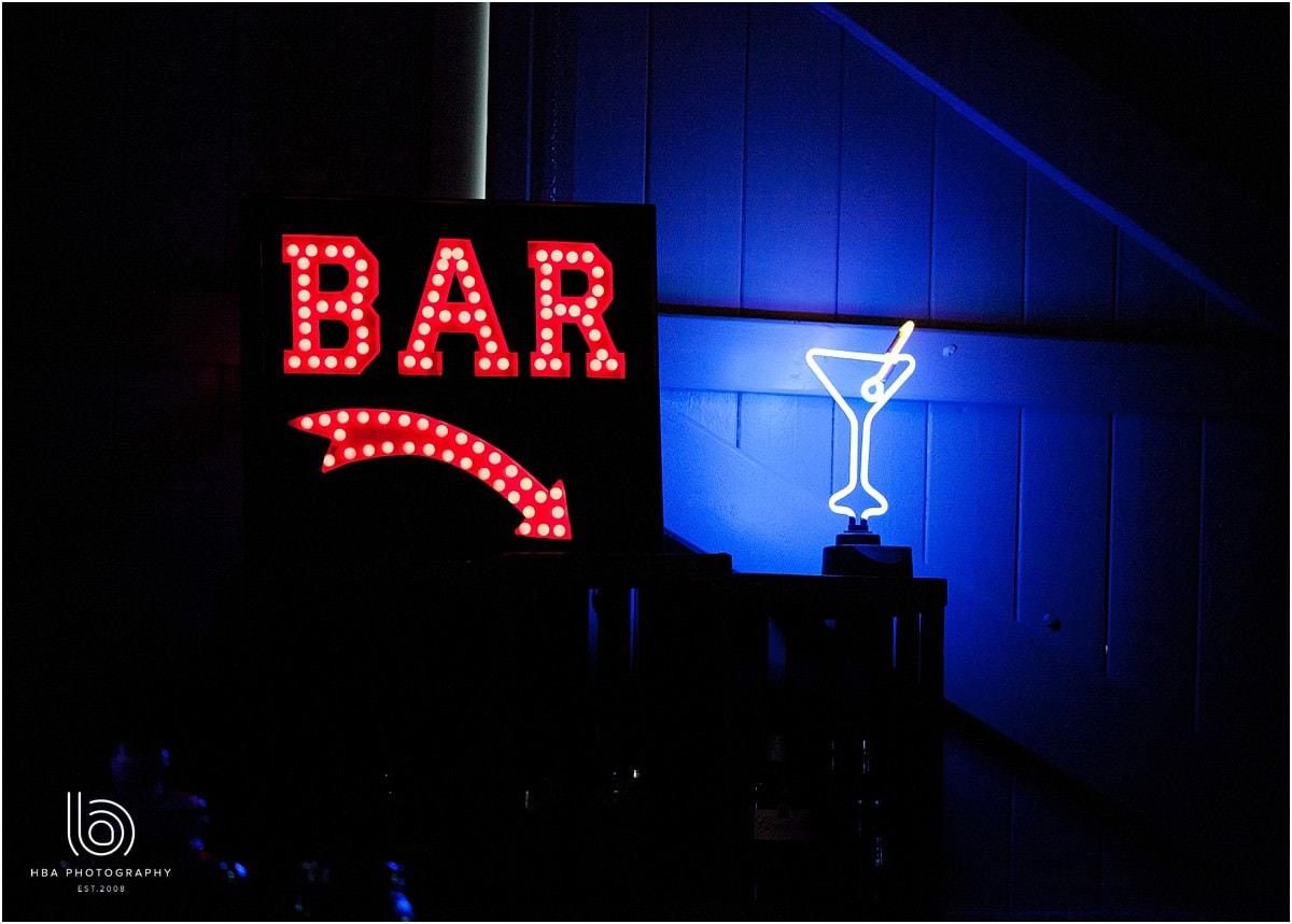 a neon bar sign at the wedding reception