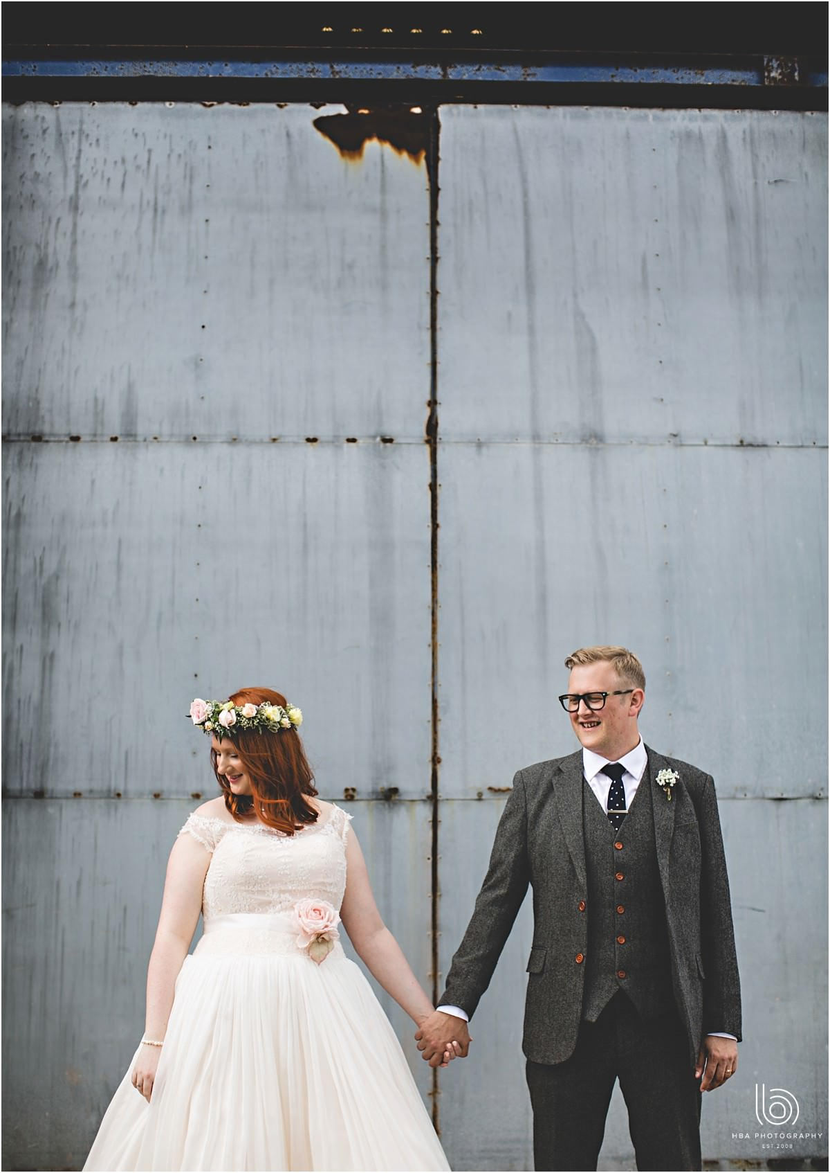 the bride and groom holding hands in front of a rustic barn door
