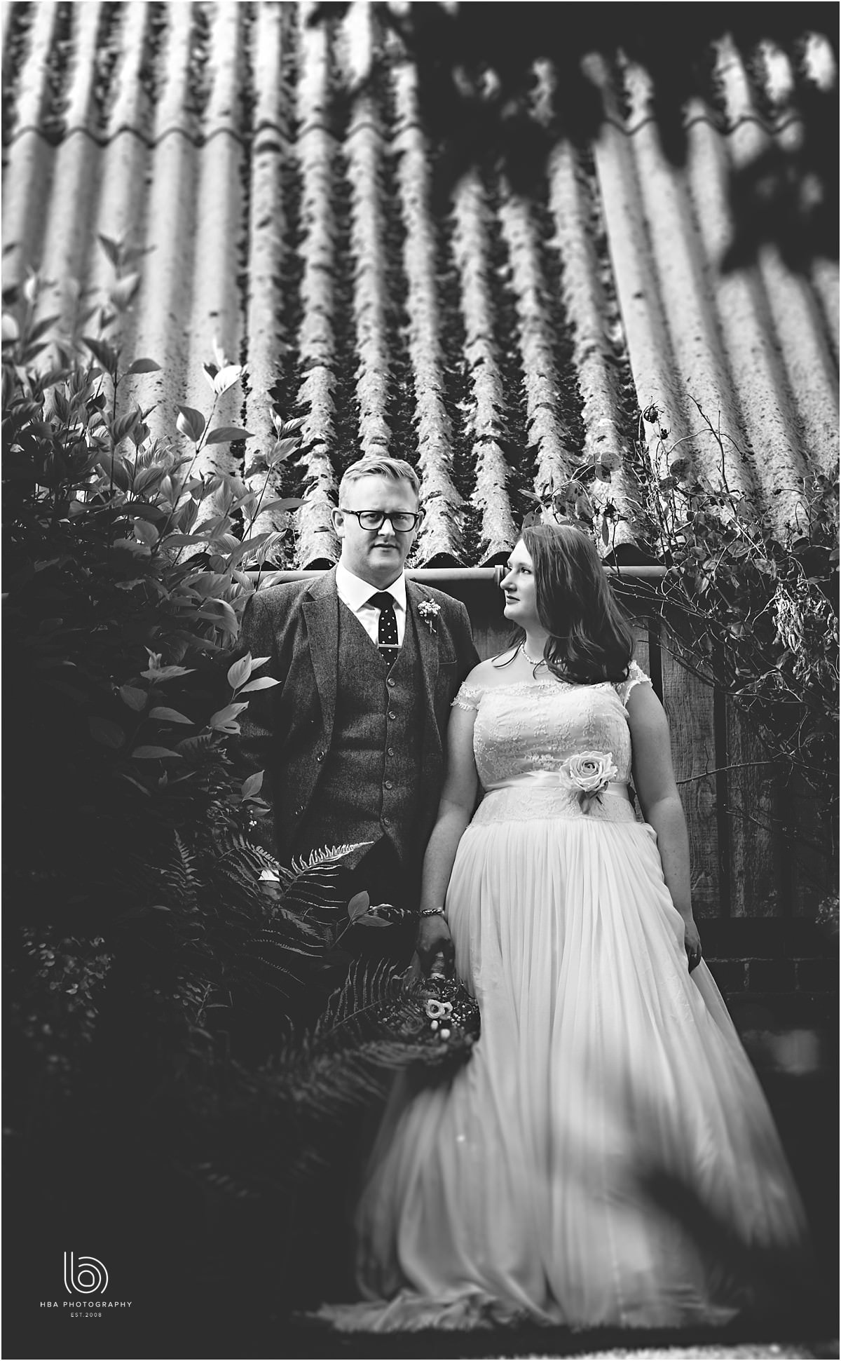 black and white photos of the bride and groom stood by a shed