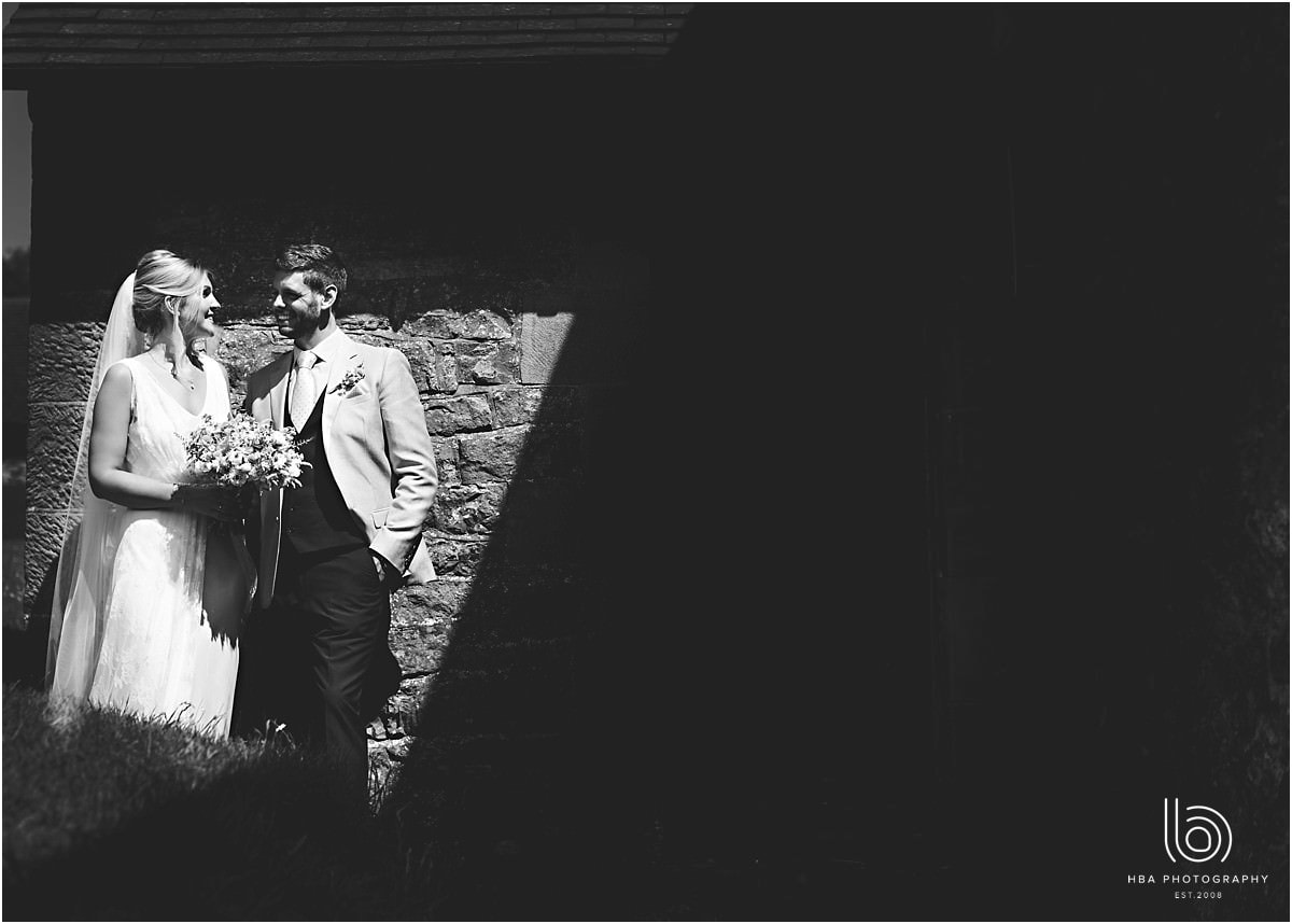the bride and groom in a pocket of light outside the church