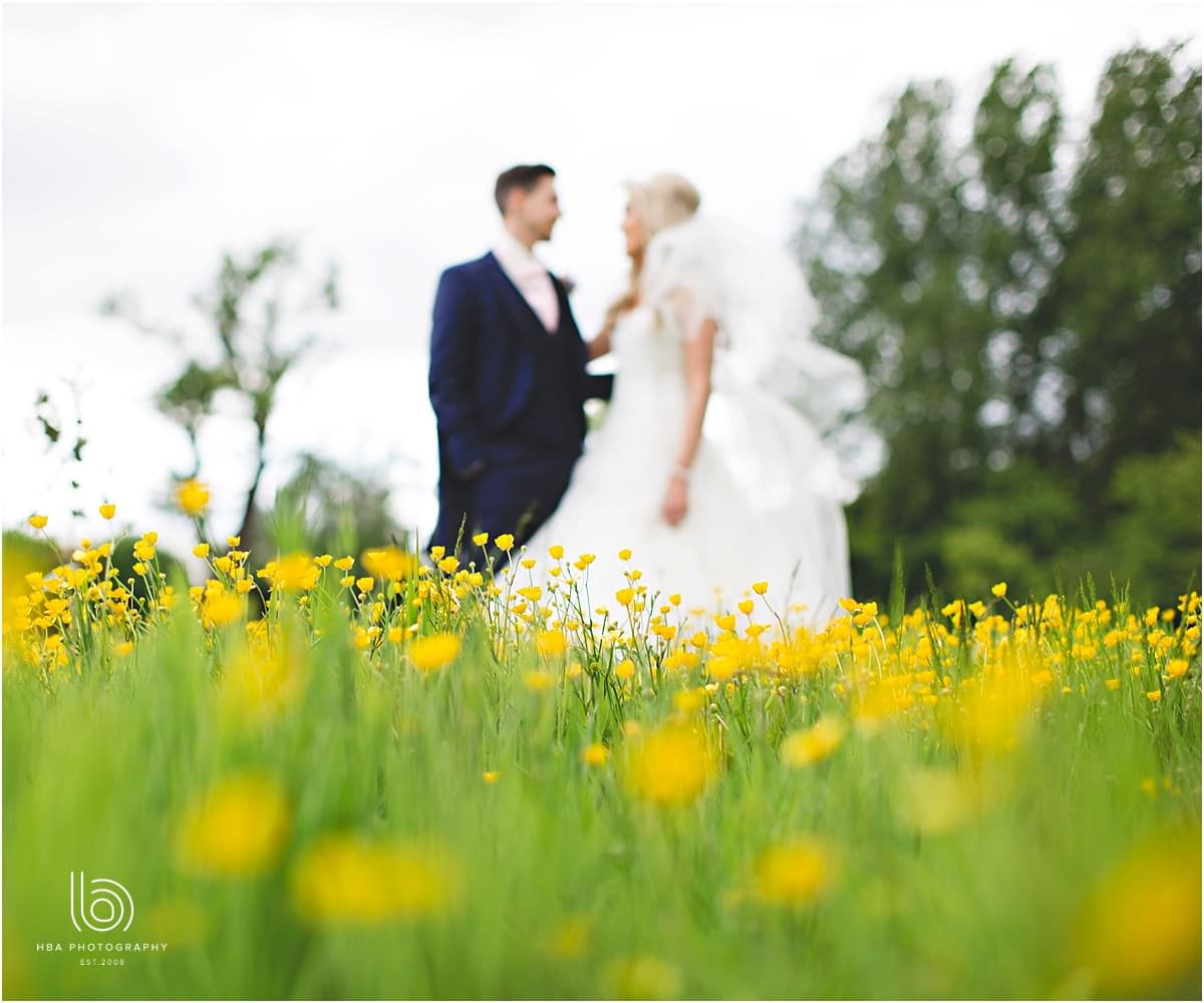 the bride and groom in a buttercup meadow