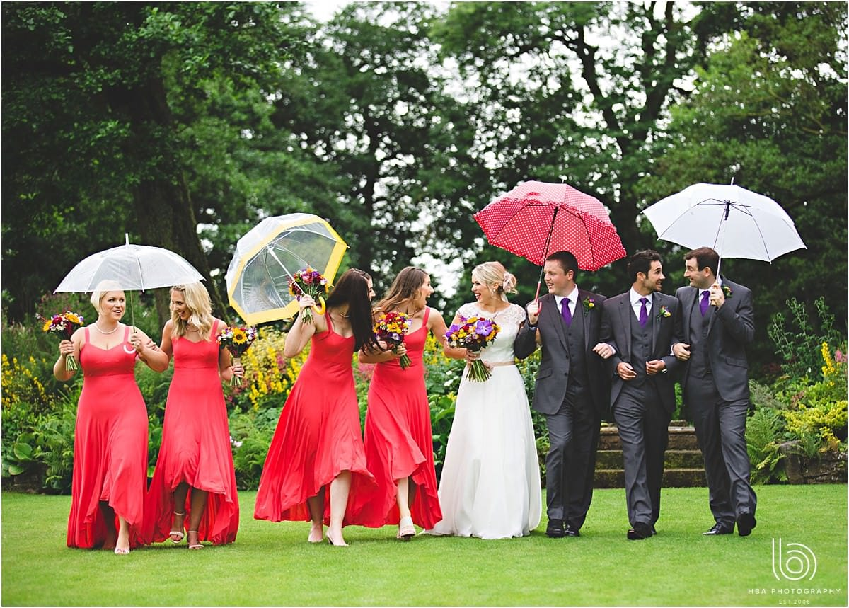 the bridal party with red umbrellas