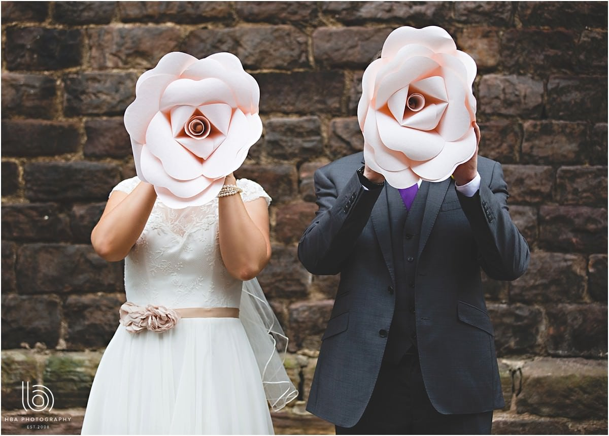 the bride and groom hiding their faces with big pink flowers