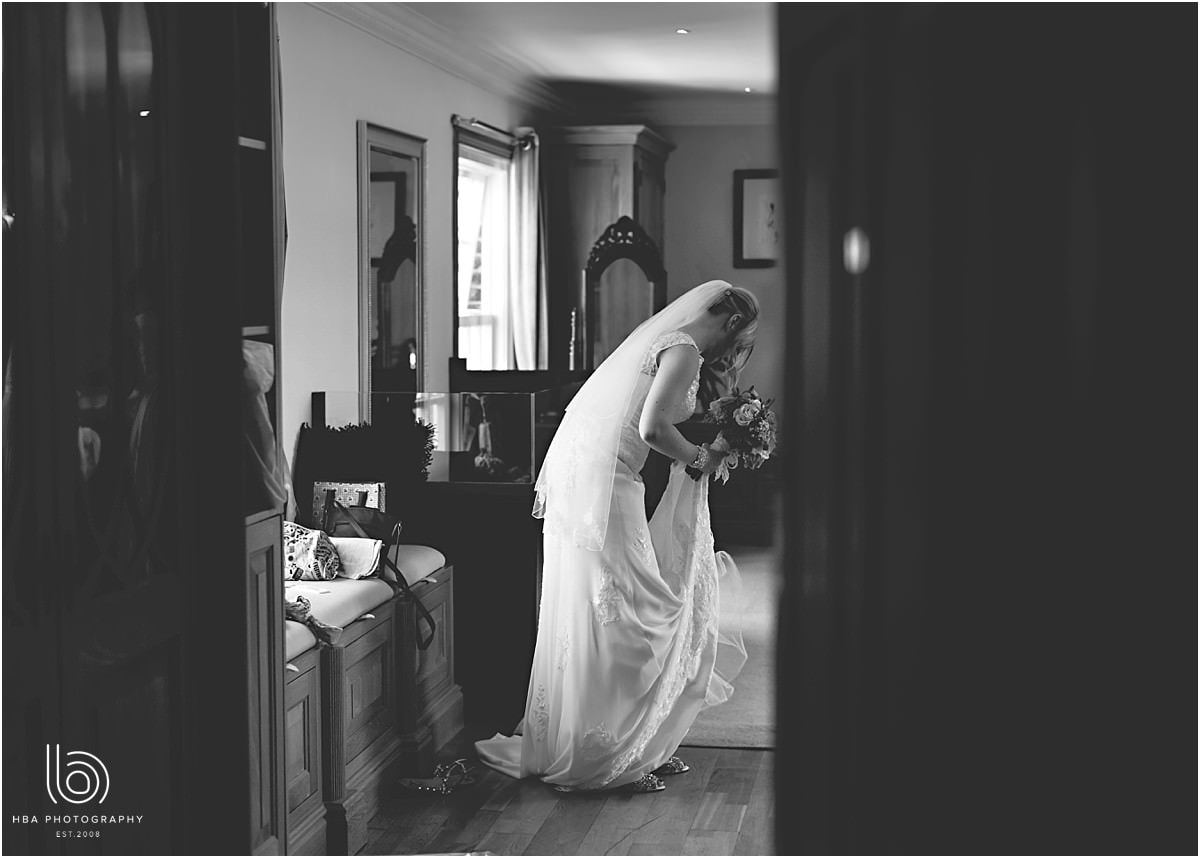 the bride getting ready, photographed through a doorway