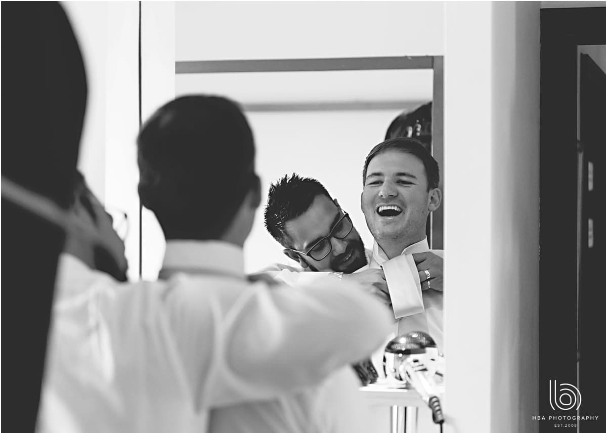 the groomsmen helping the groom get ready