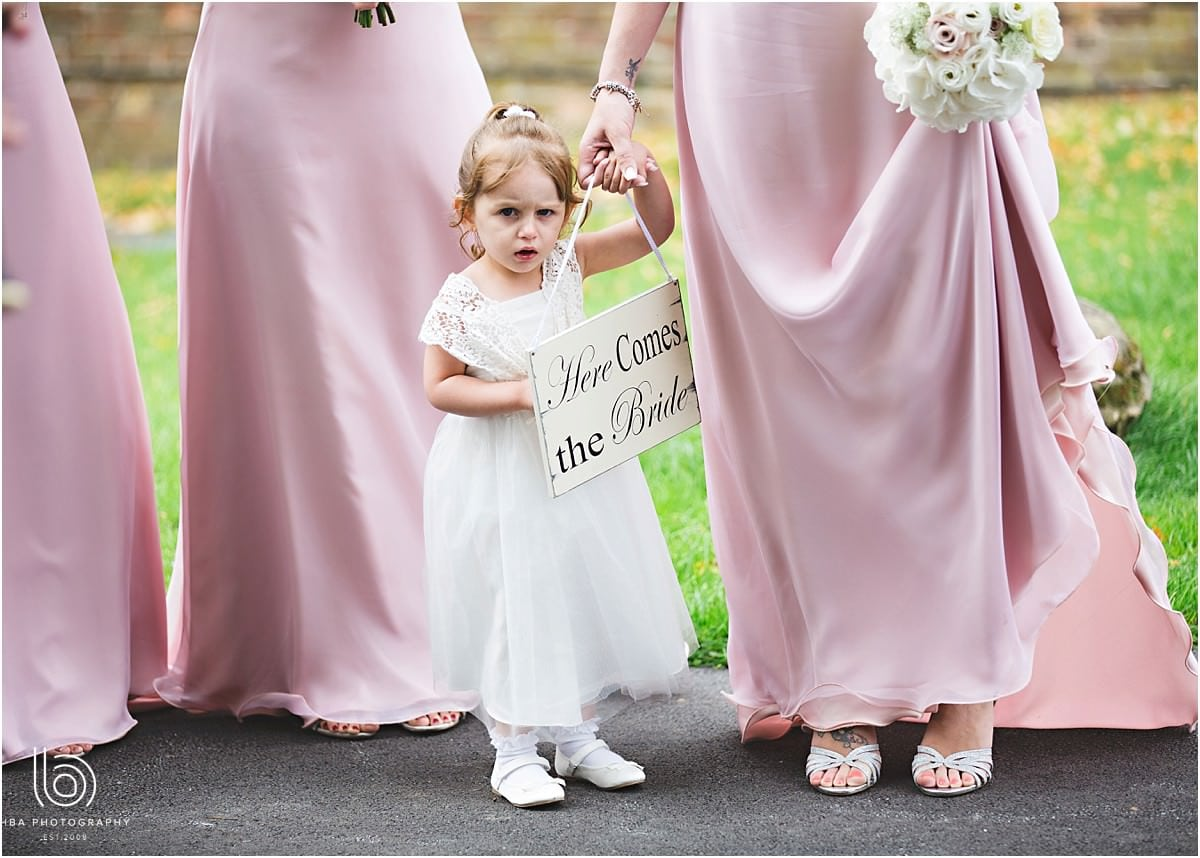 a small flower girl holding a wedding sidn