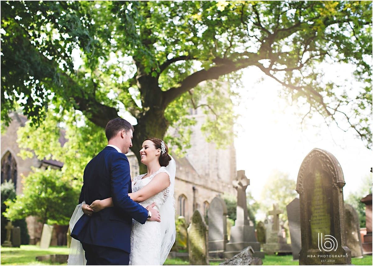 the bride and groom hugging in the church yard in the sun