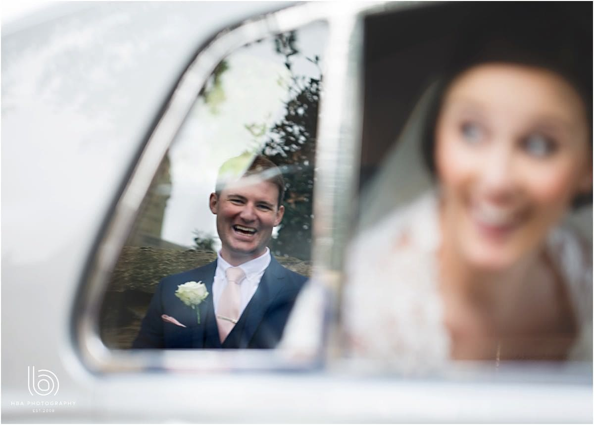 a reflection of the groom in the car window