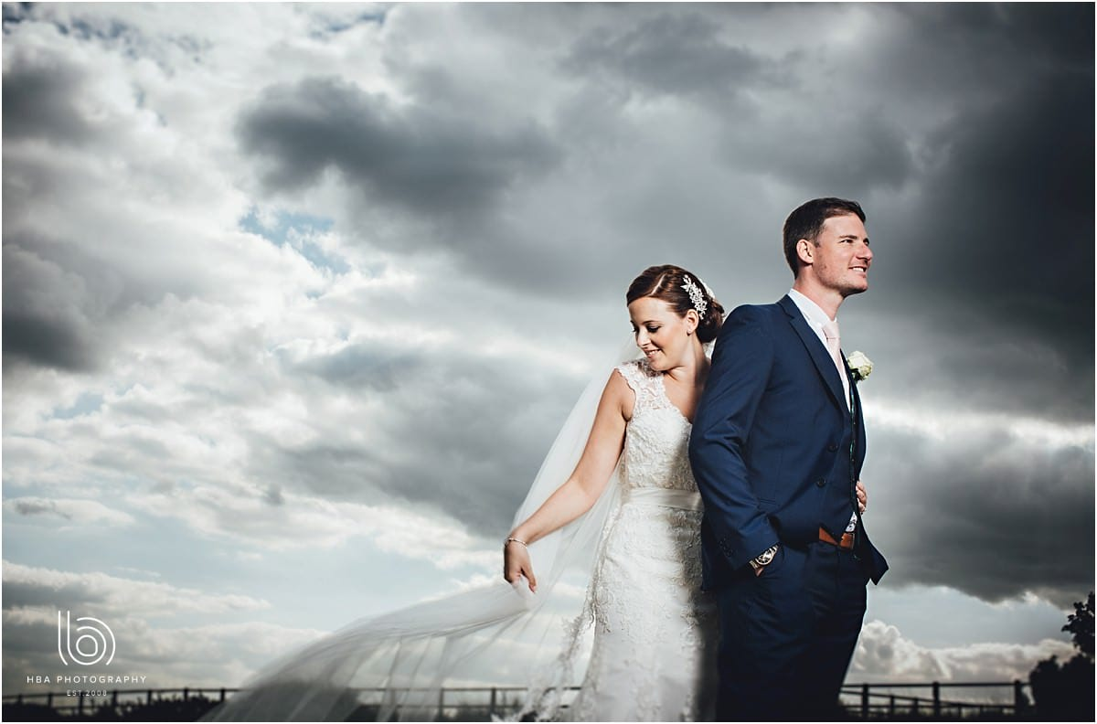 bride and groom stood with a dramatic sky