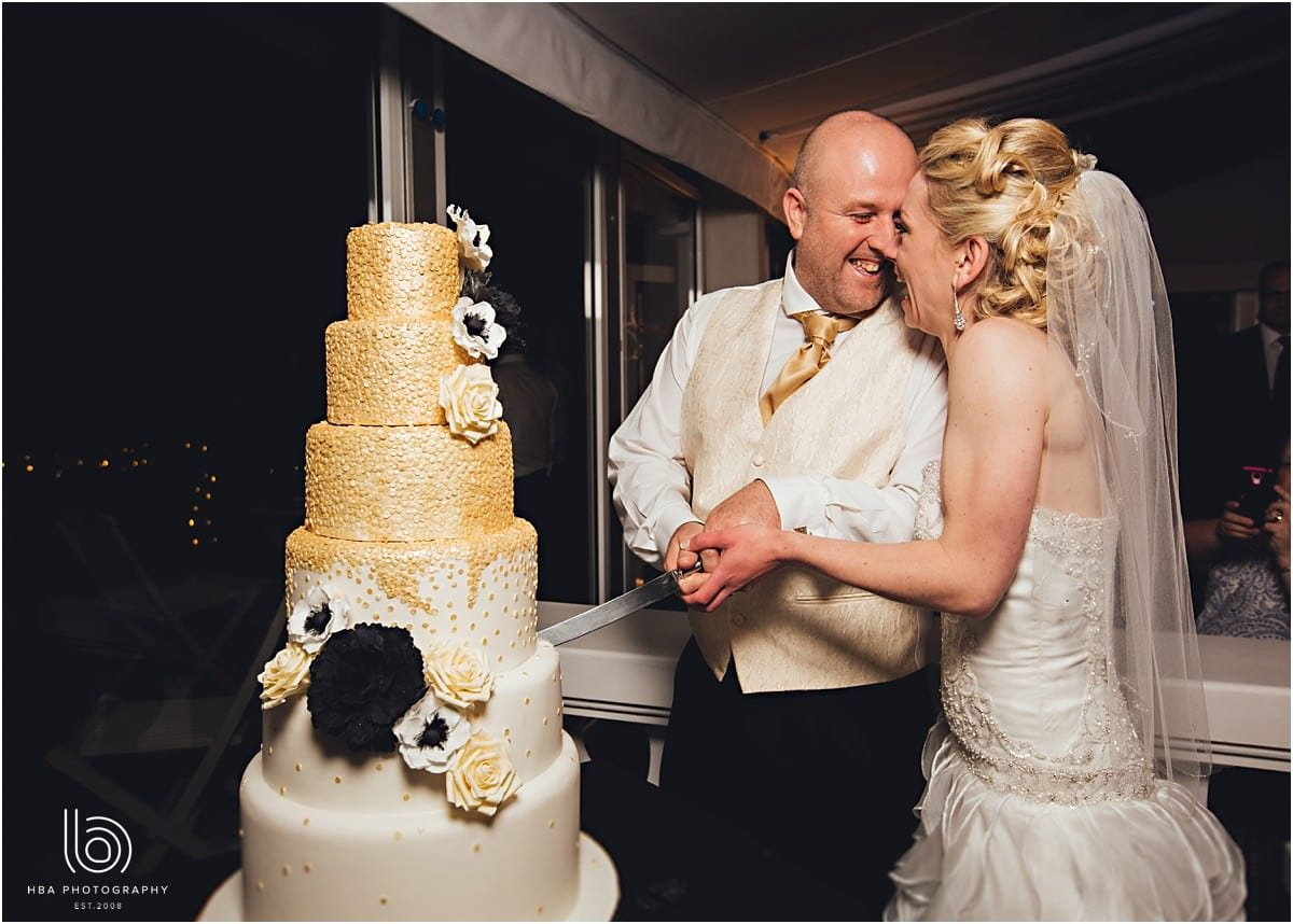 the bride and groom with their gold wedding cake