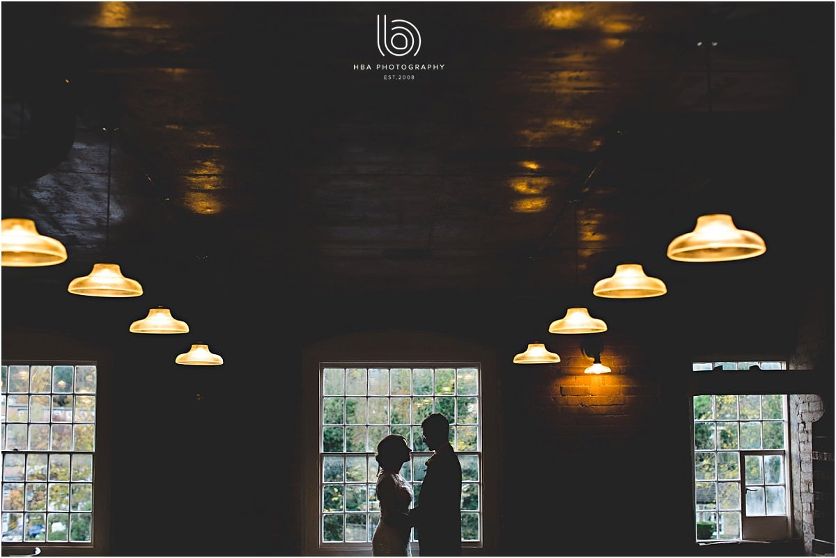 a silhouette of the bride & groom against a window