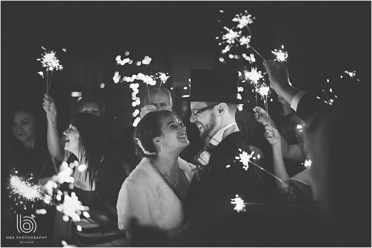 the bride and groom with sparklers in the evening