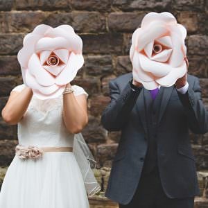a couple holding giant flowers on their wedding day