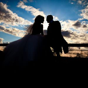 A silhouette of a bride and groom with a dramatic sky