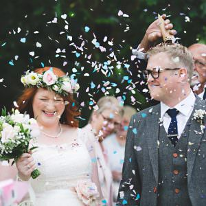 a bride and groom getting covered in confetti