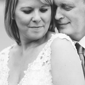 A black and white photo of a couple close together hugging