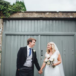 A bride and groom holding hands by a green wall