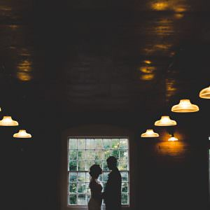 A dark photo of a bride and groom stood by a window with orange lights