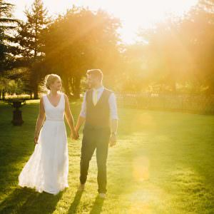 a bride and groom walking holding hands in the sunshine