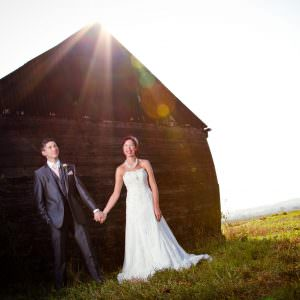 A bride and groom stood by an old shed