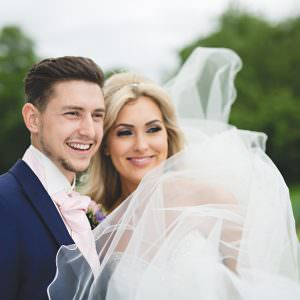 a bride and groom smiling as her veil blows in the wind
