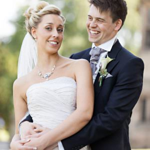 A groom giving his wife a cuddle