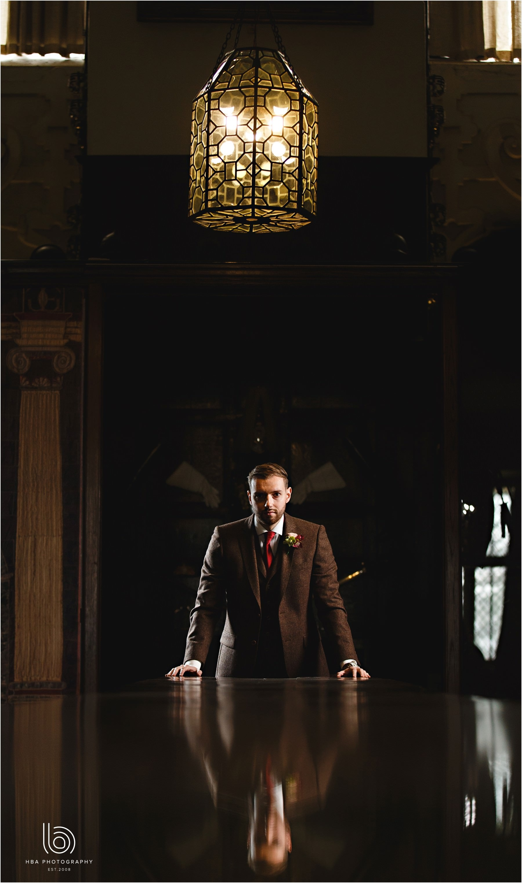 Groom stood in the dark by a reflective table