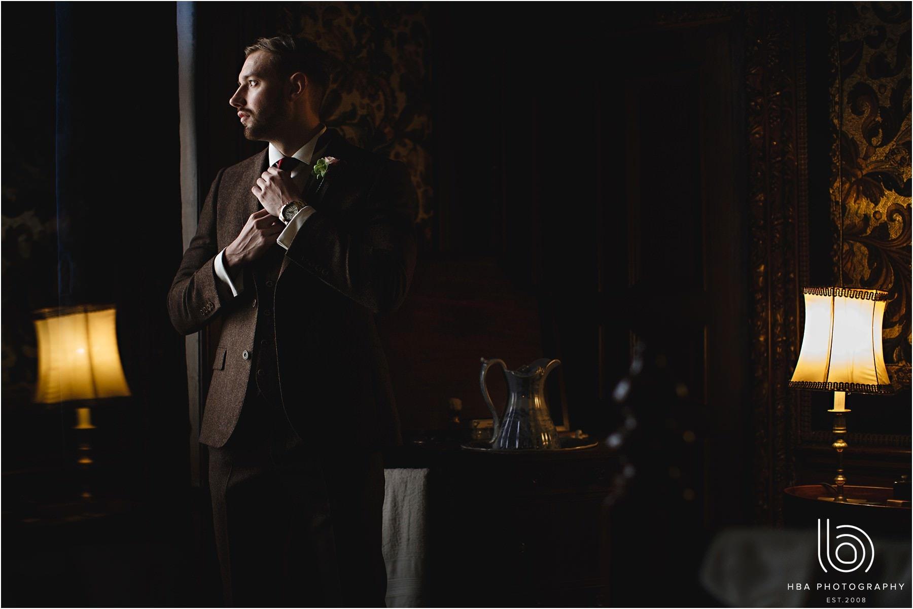 groom adjusting his tie in the window