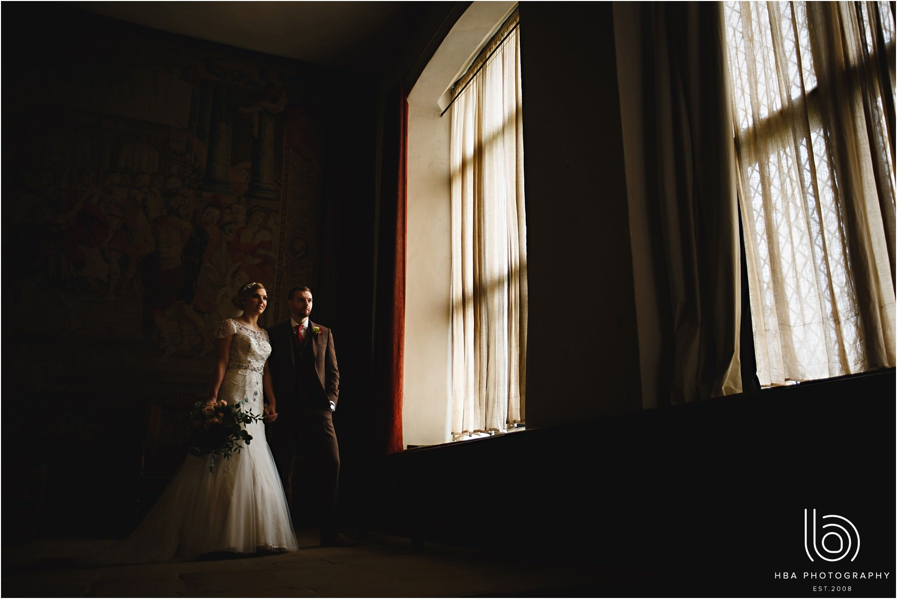 the bride and groom stood by the big windows at Hardwick Hall