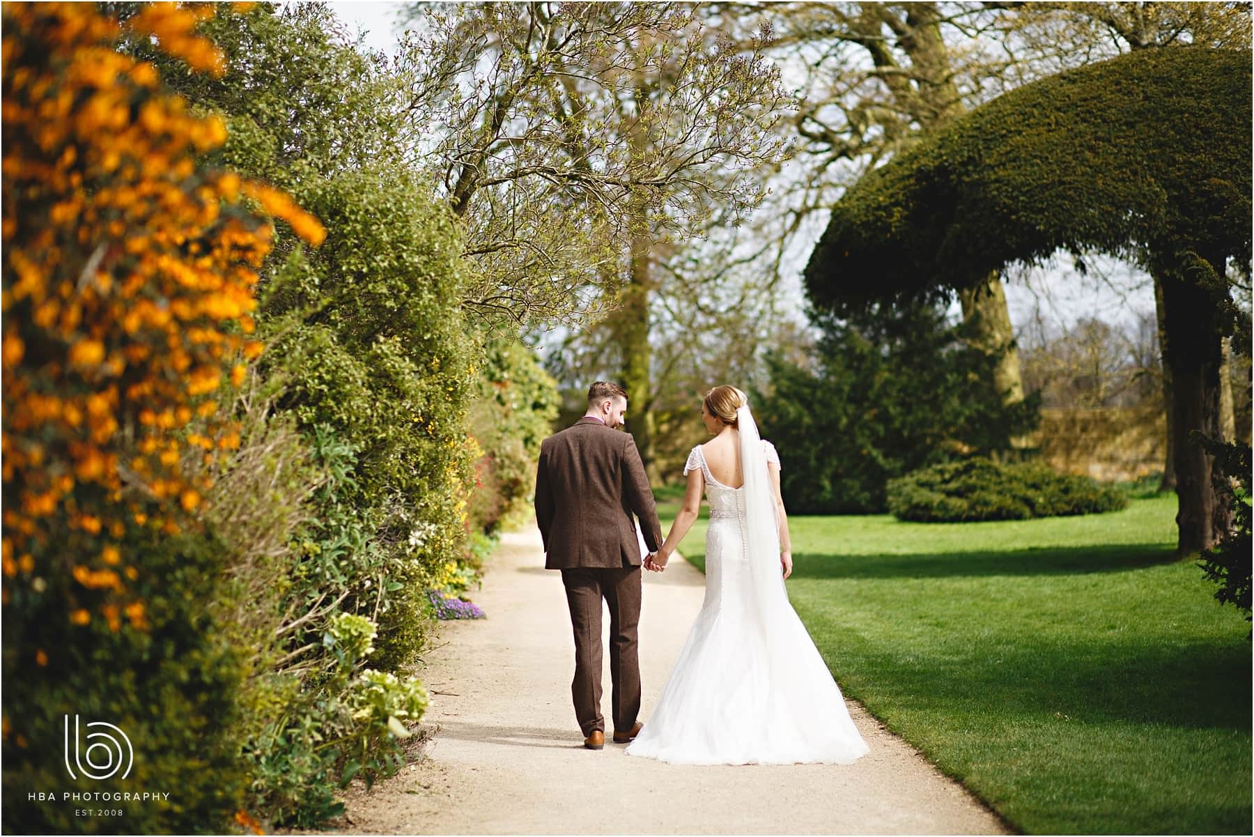 The bride and groom walking down the garden paths at Hardwick Hall