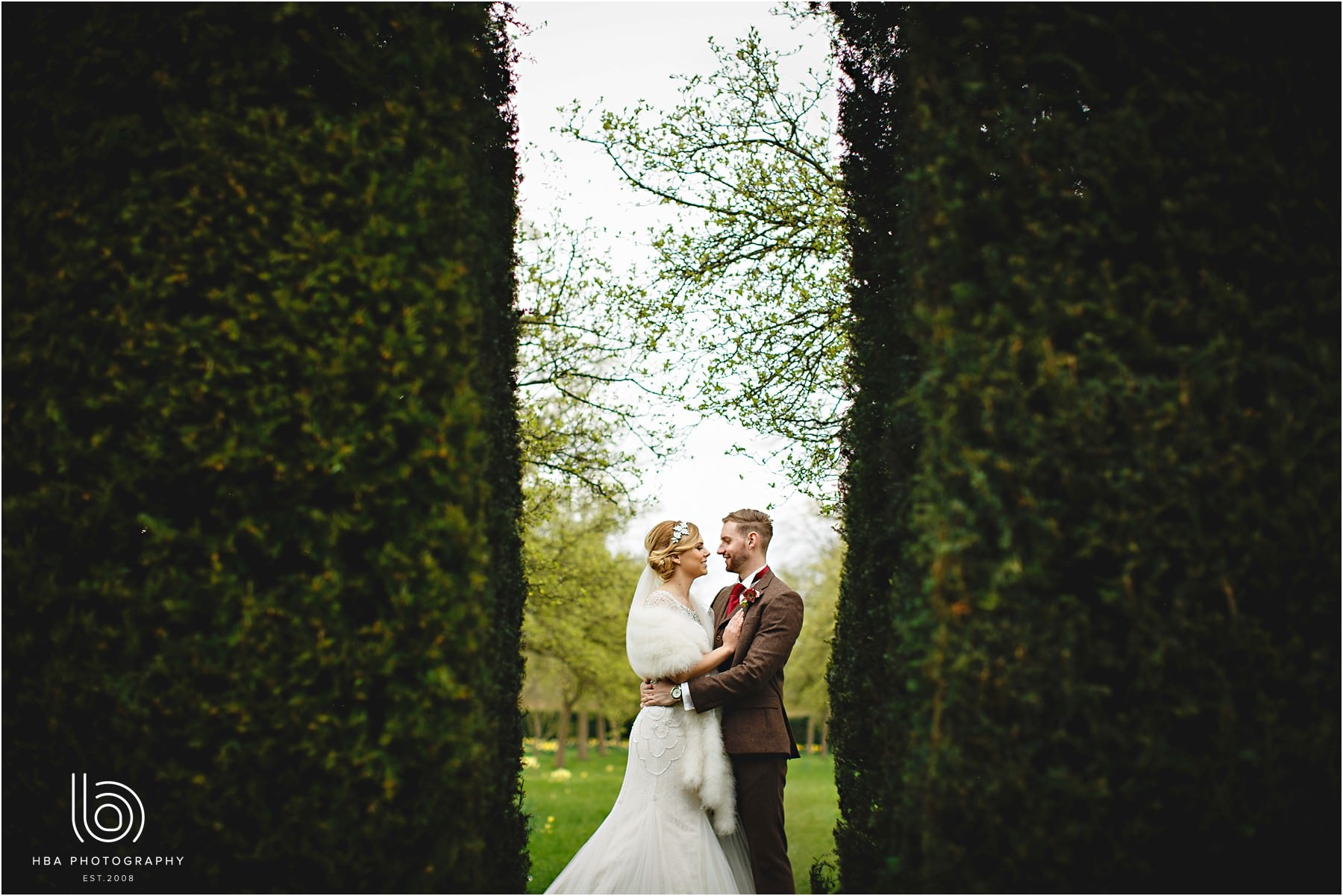 The bride and groom in the talll green hedges at Hardwick Hall