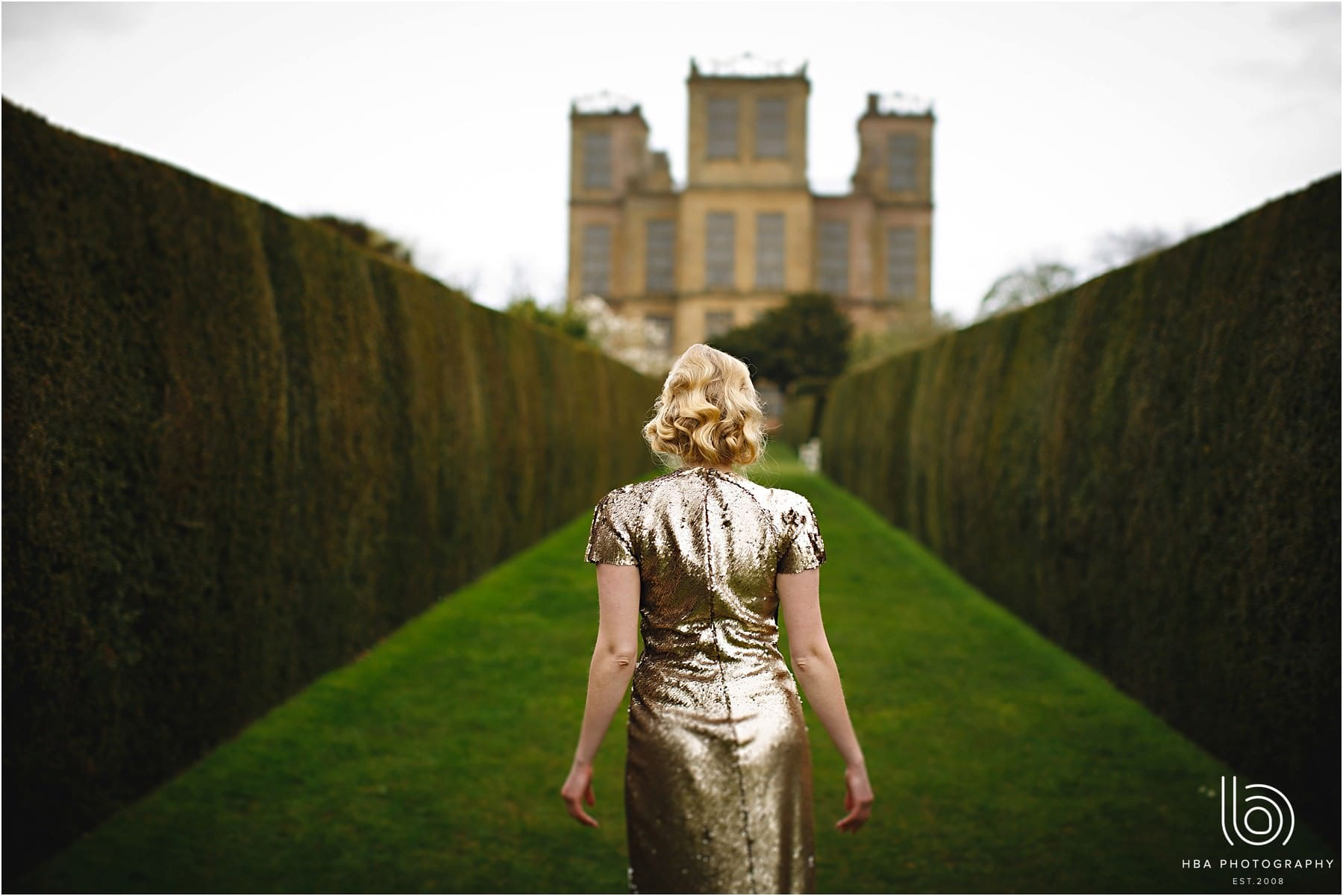 the bride in a gold wedding dress walking towards Hardwick Hall