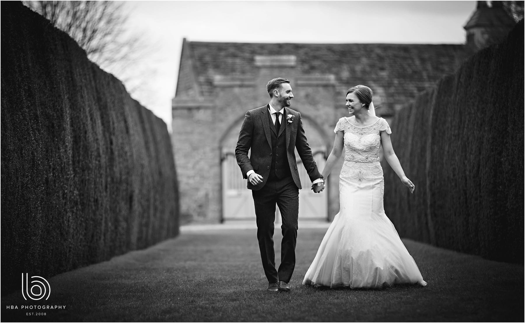 The bride and groom wlaking towards Hardwick Hall on their wedding day