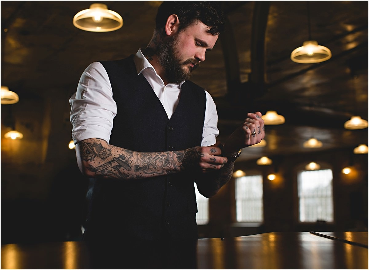 a groom with tattoos adjusting his watch