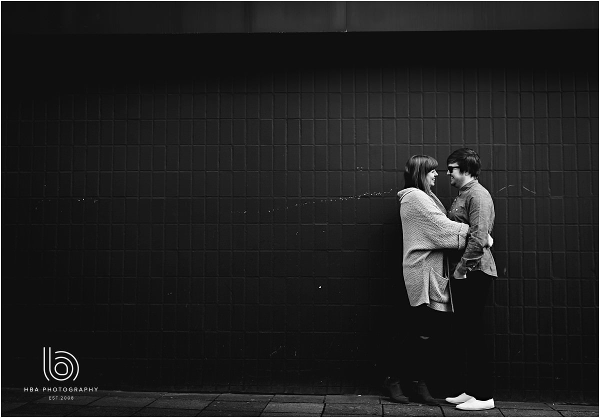 black and white picture with an engagement couple stood by a black wall