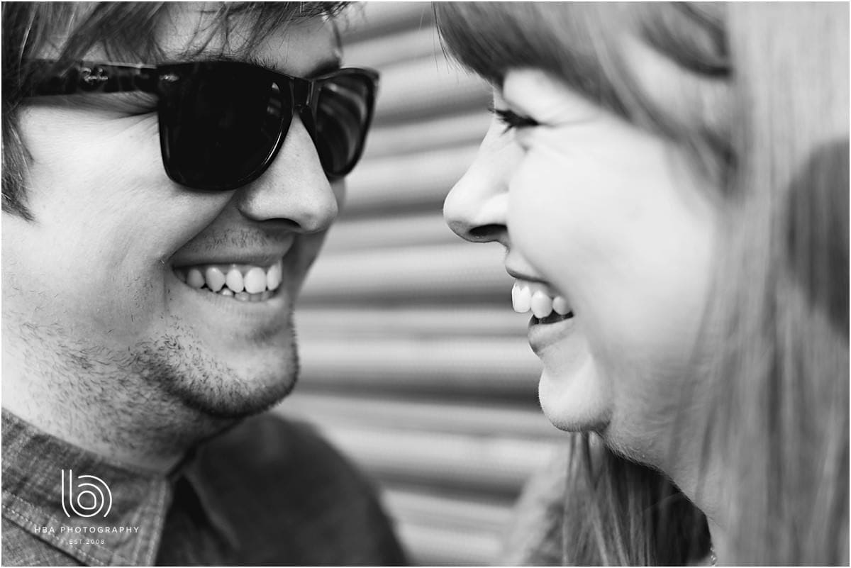 engaged couple in black sunglasses smiling at each other