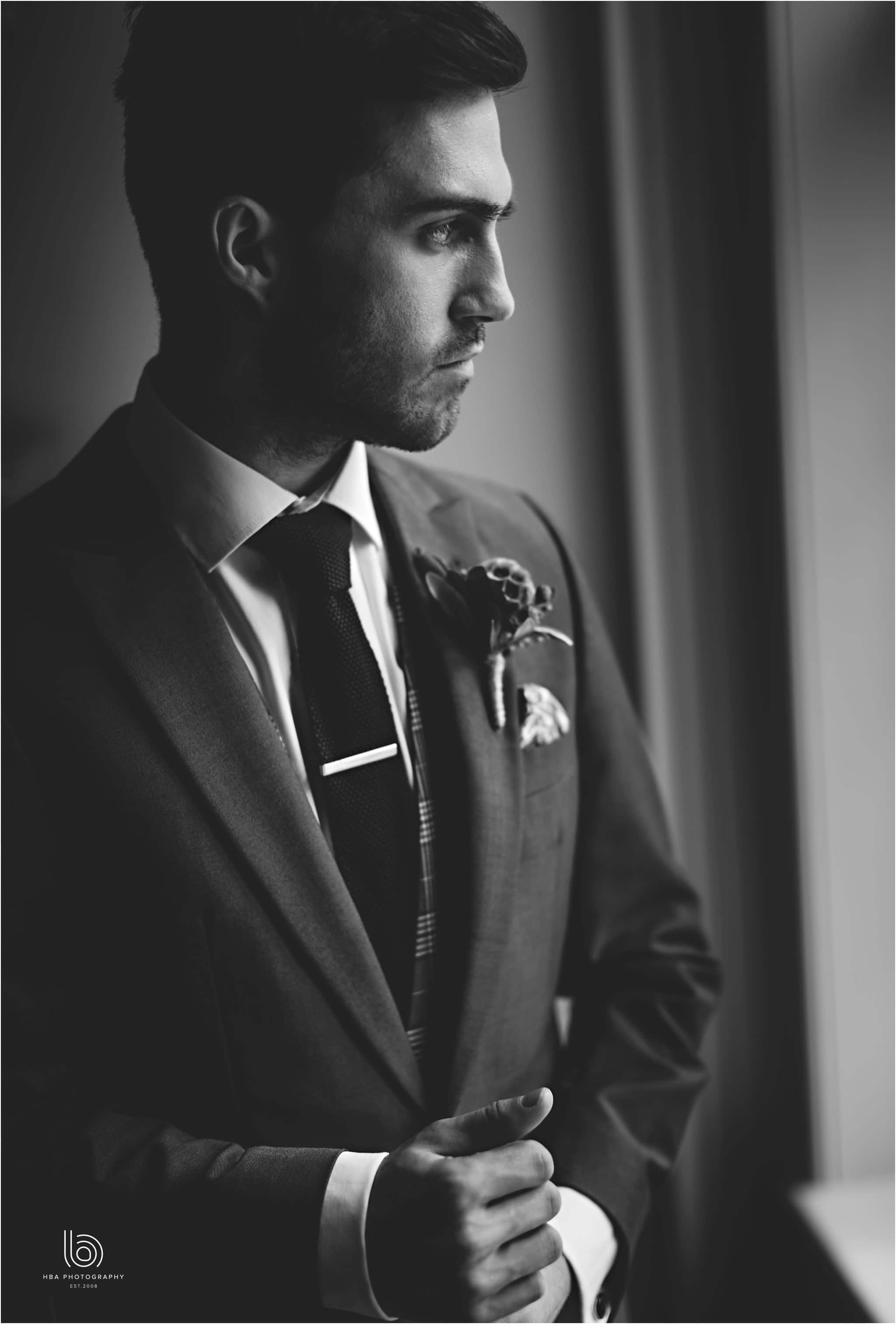the groom in blavk and white stood by a window at Dorfold Hall