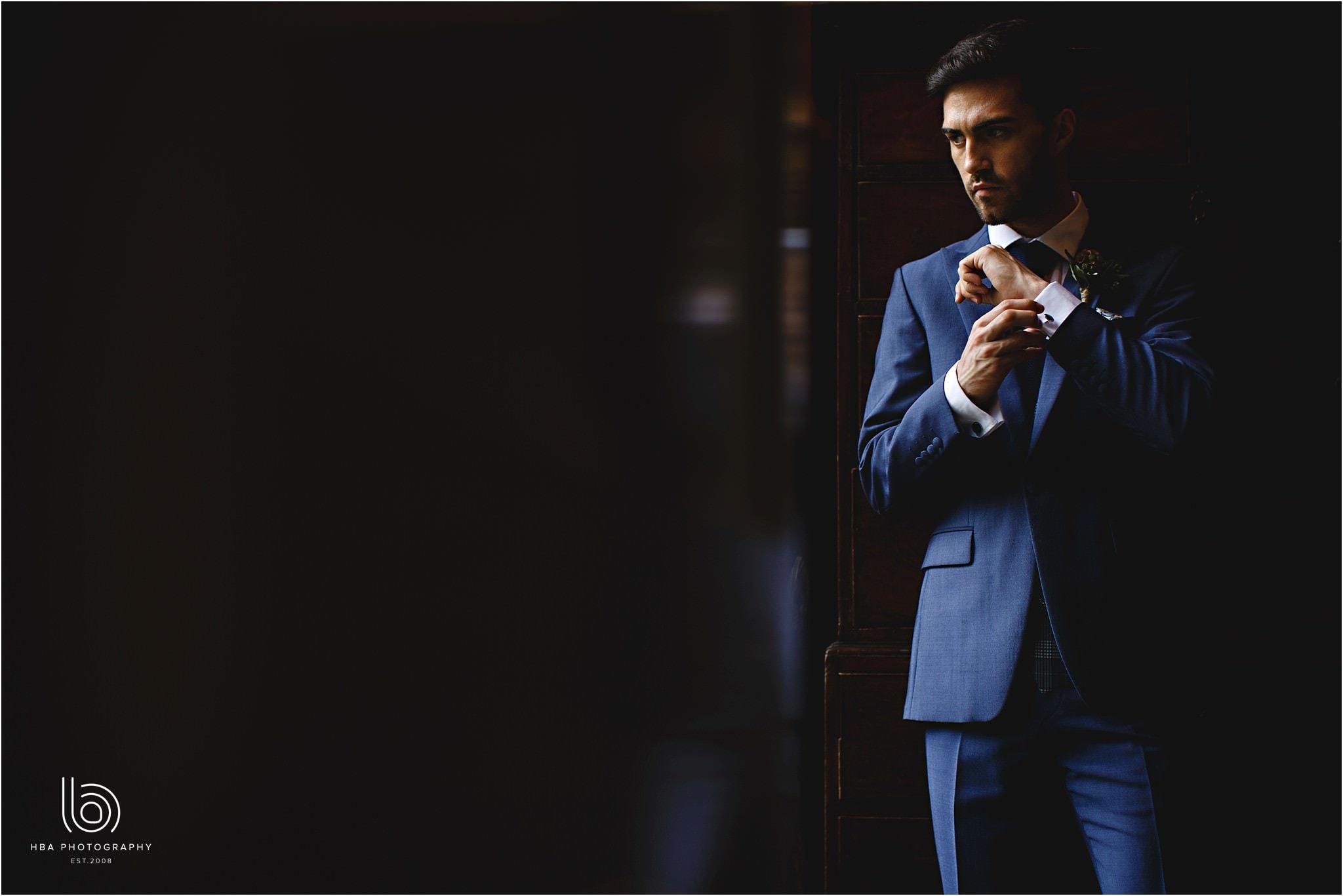 the groom stood in window light in a blue suit