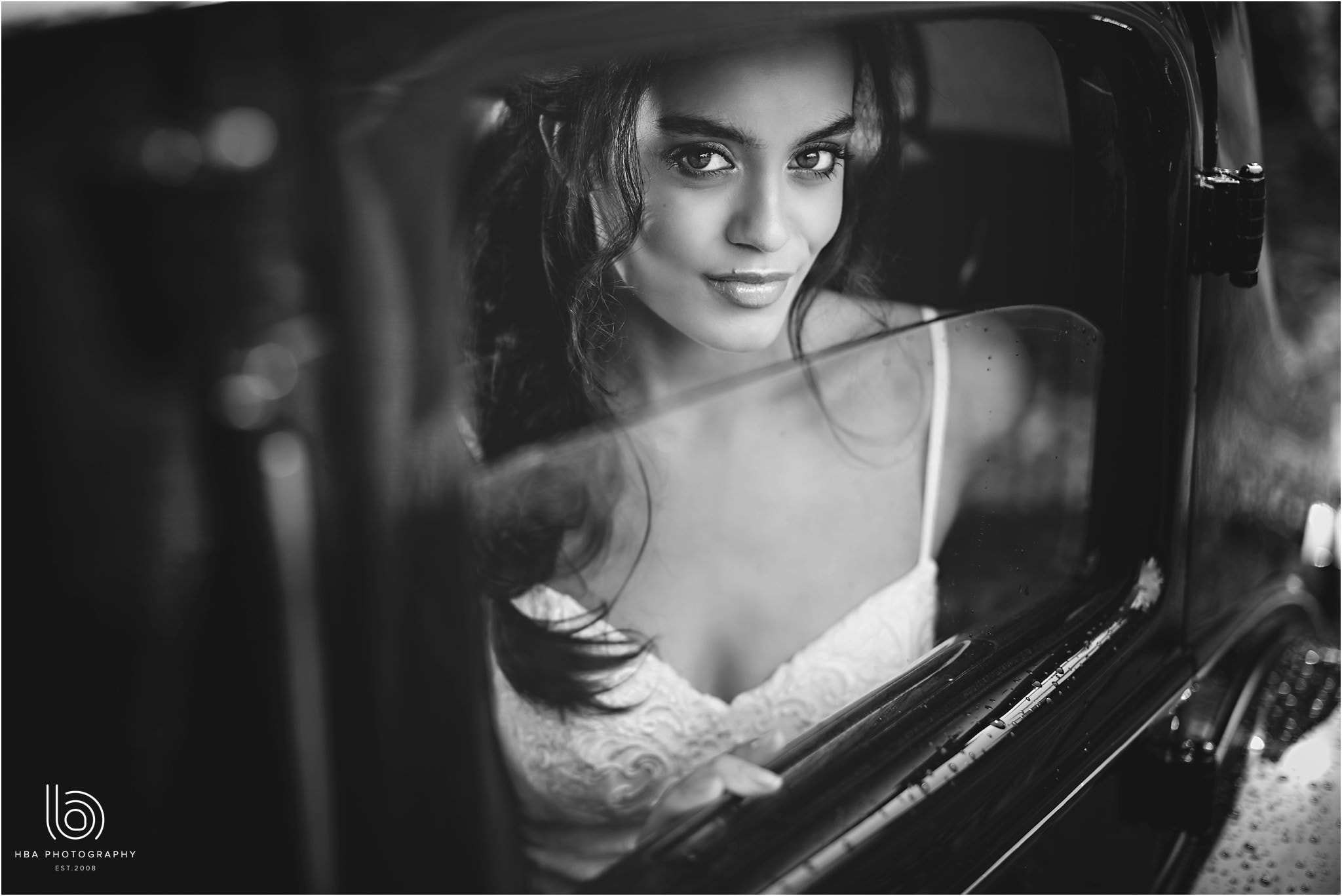 a black and white photo of the bride looking out of the car window